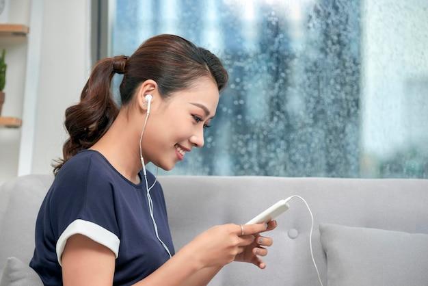 이어폰을 끼고 집에서 스마트폰으로 메시지를 보내는 행복한 젊은 아시아 여성. 회색 소파에 편안하게 앉아 음악을 들으며