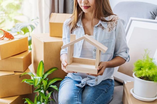 Счастливая молодая азиатская женщина в гостиной в новом доме со стопкой картонных коробок в переездной день