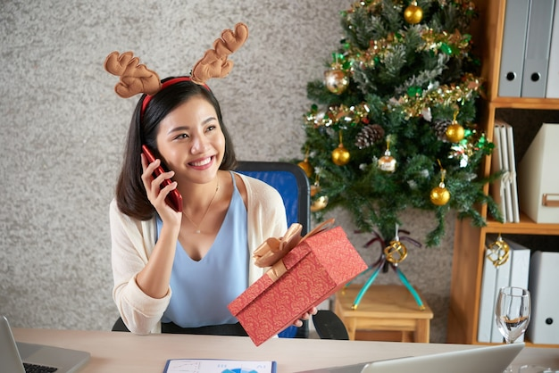 Счастливая молодая азиатская женщина в ободке из оленей держит рождественский подарок и разговаривает по телефону