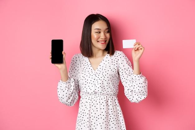 幸せな若いアジアの女性のインターネットショッピング、スマートフォンの画面を表示し、クレジットカードで満足している