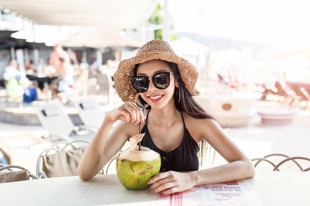 Happy young asian woman is enjoying coconut drink in the beach bar, phuket province, thailand