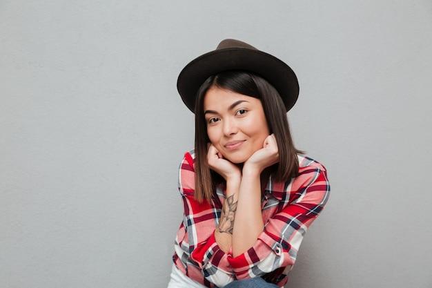 灰色の壁に分離された幸せな若いアジア女性
