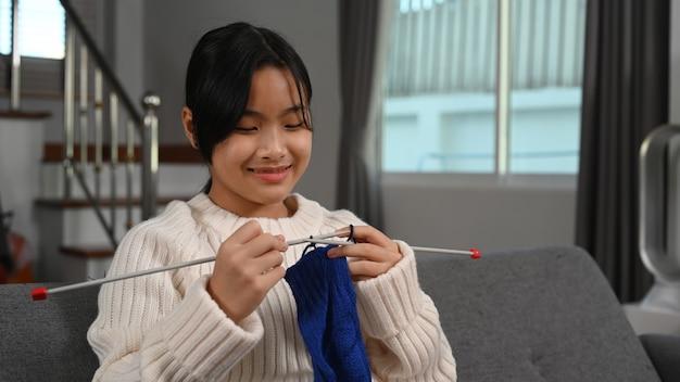 거실에 앉아 파란색 스웨터를 뜨개질하는 행복한 젊은 아시아 여성.