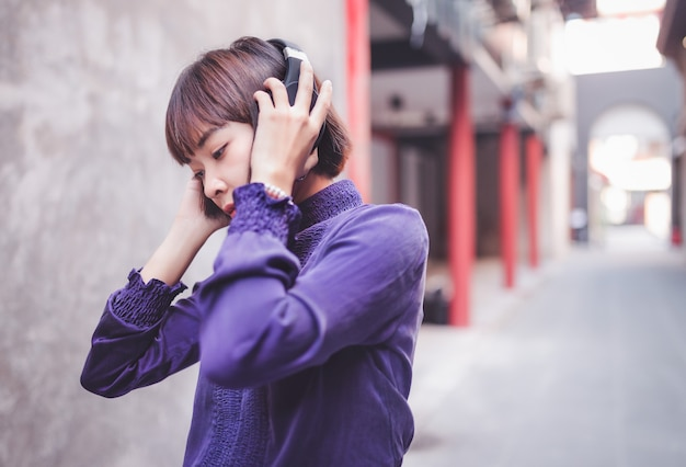 Happy young asian woman listening to music with headphones on the street.