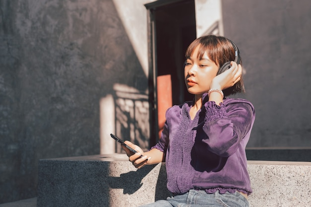 Happy young asian woman listening to music with headphones via smartphone and having fun while sitting side the street.