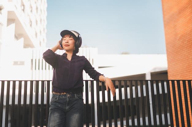 音楽を聴いて、路上でヘッドフォンを楽しんで幸せな若いアジアの女性。