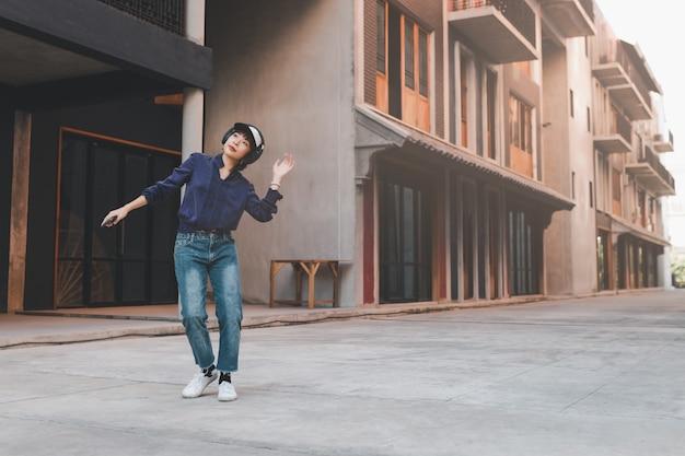 音楽を聴いて、路上でスマートフォンを介してヘッドフォンを楽しんで幸せな若いアジアの女性。
