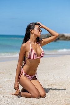 Счастливая молодая азиатская женщина на пляже. внешний портрет моды девушки наслаждаясь ее каникулами в горячем тропическом острове. сексуальная идеально облегающая тело женщина.