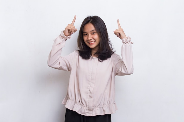 Happy young asian woman pointing with fingers to different directions isolated on white background