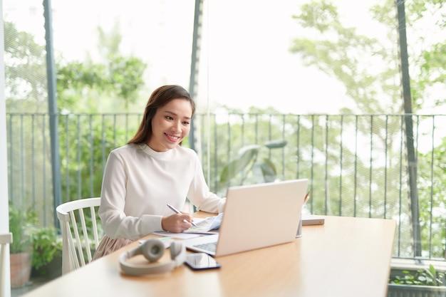 Счастливая молодая азиатская женщина расслабляется, сидя на столе, делает работу в интернете