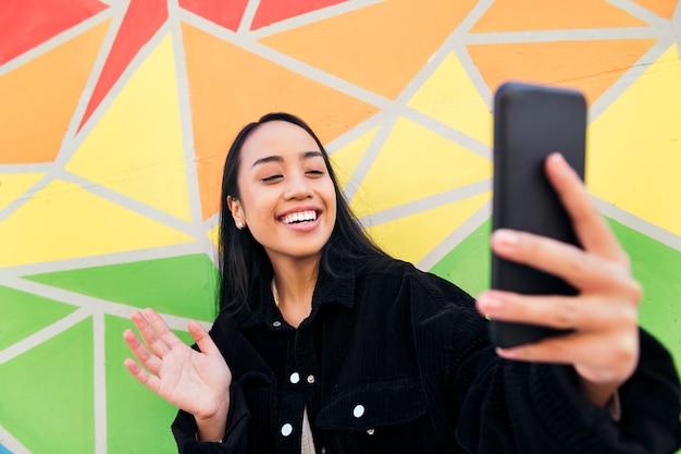행복한 젊은 아시아 여성이 화려한 벽 옆에서 휴대전화로 화상 통화를 하고 손으로 인사한다
