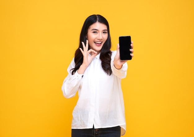 Счастливая молодая азиатская женщина показывая на одобренном жесте мобильного телефона пустого экрана и изолированном над желтым фоном.