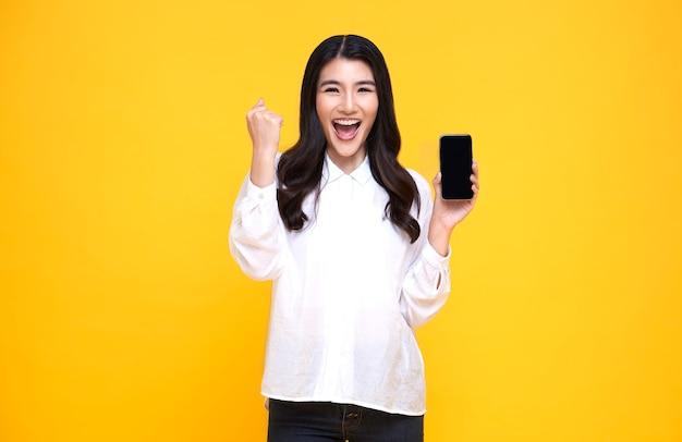 Счастливая молодая азиатская женщина показывая на мобильном телефоне пустого экрана и успехе жеста руки изолированном над желтым фоном.