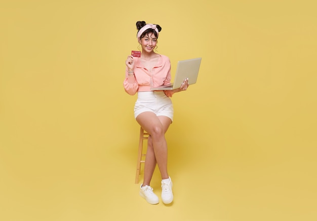 Happy young asian woman showing credit card and using computer online shopping isolated over yellow background.
