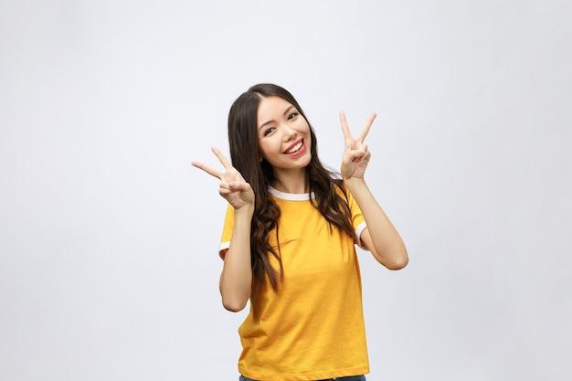 2本の指または勝利のジェスチャーを示す幸せな若いアジアの女性