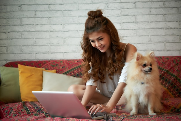 Happy young asian woman sitting on couch at home with small pet dog and using laptop