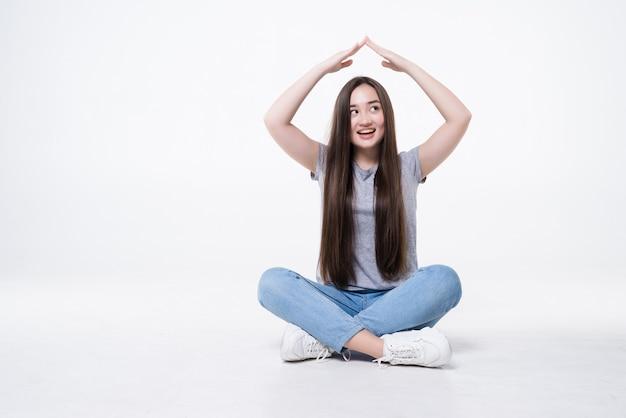 Felice giovane donna asiatica seduta sul pavimento con il gesto del tetto sul muro bianco