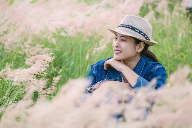 芝生の上に座って幸せな若いアジア女性