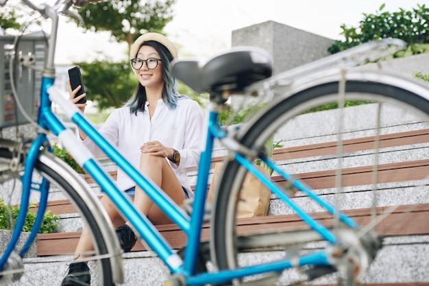 Счастливая молодая азиатская женщина сидит на ступеньках и делает селфи после поездки на велосипеде