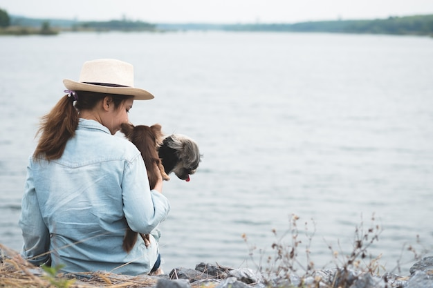 リザーブの横に彼女の犬と一緒に座っている幸せな若いアジアの女性。