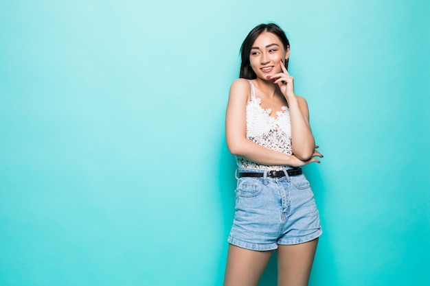 Happy young asian woman standing on green wall