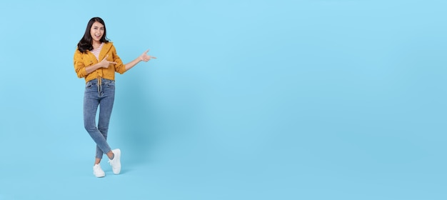 Happy young asian woman standing with her finger pointing isolated on blue background with copy space. panoramic background.