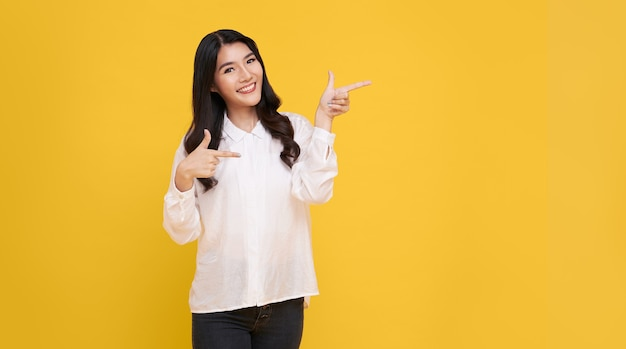 Happy young asian woman standing with her finger pointing isolated over yellow banner background with copy space.