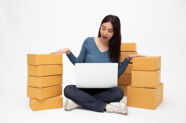 Счастливый молодой азиатский запуск независимого малого бизнеса женщины с компьтер-книжкой компьютера и сидеть на изолированном поле, онлайн концепции поставки коробки упаковки маркетинга