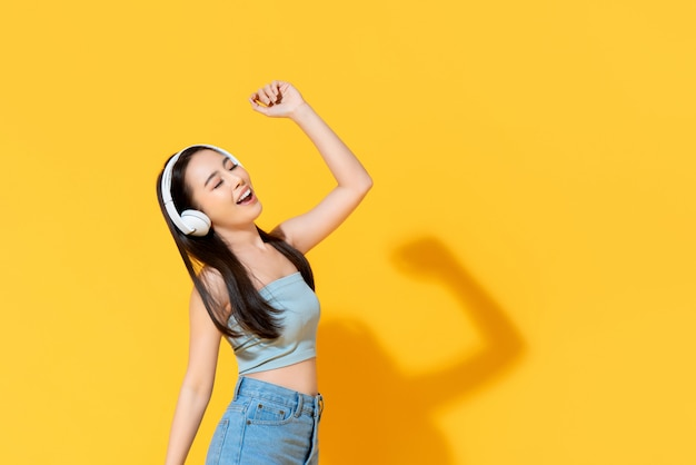 Happy young asian woman in summer wear listening to music from headphones and dancing isolated