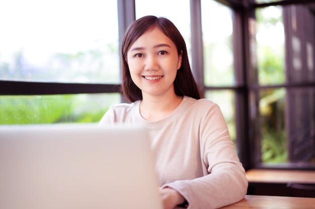 コーヒーショップのワークスペースで働くためにラップトップコンピューターを使用して幸せな若いアジアの女性は、コピースペースでクローズアップ。