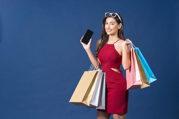 파란색 배경에서 온라인 쇼핑을 위해 휴대전화를 사용하는 행복한 젊은 아시아 여성