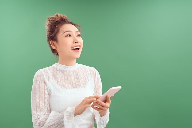 Счастливая молодая азиатская женщина с помощью мобильного телефона, глядя вверх. изолированные на зеленом фоне.