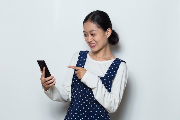 Happy young asian woman using mobile phone