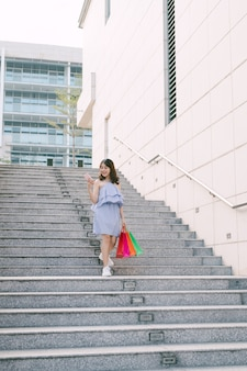 Happy young asian woman using phone and going down stairs with colorful shop packages.