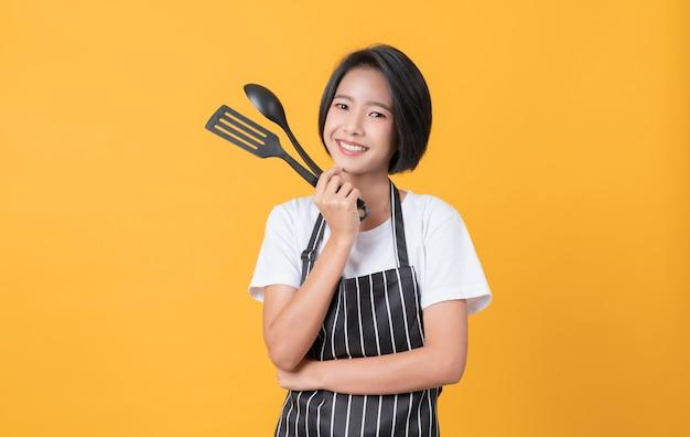 행복한 젊은 아시아 여성은 앞치마를 입고 밝은 노란색 배경에 냄비가 있는 주걱을 보여줍니다.