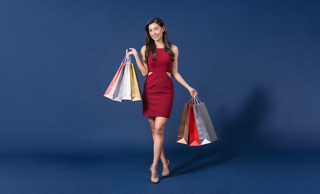 青い色のマルチカラーの買い物袋を運ぶ赤いドレスを着て幸せな若いアジアの女性
