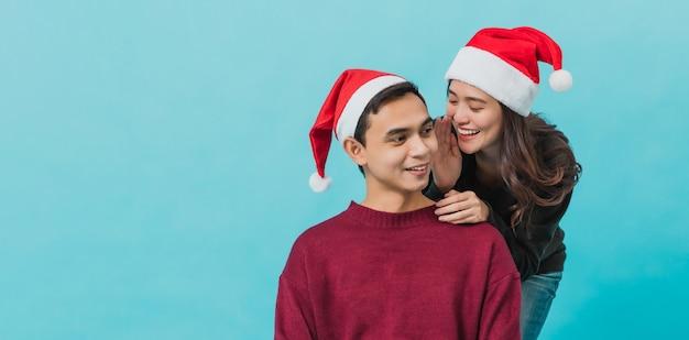 サンタクロースを着て、彼女のボーイフレンドにささやく幸せな若いアジアの女性