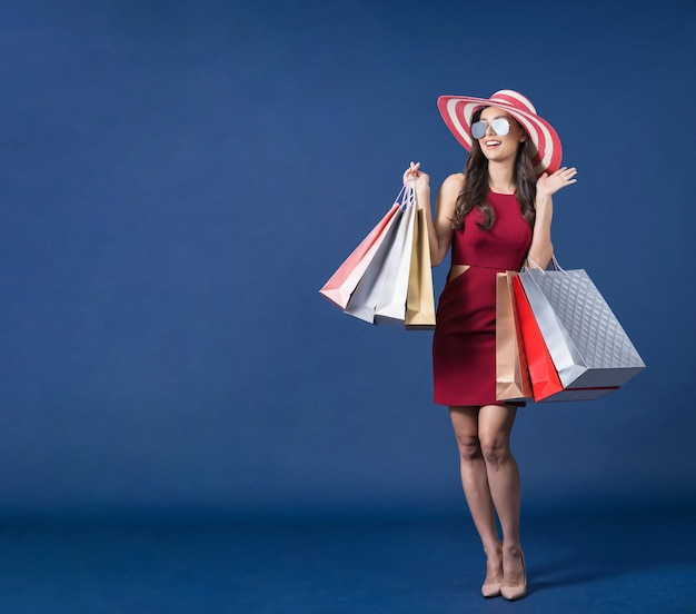 サングラスをかけ、マルチカラーの買い物袋を運ぶ幸せな若いアジアの女性