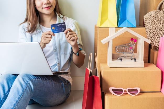 カラフルなショッピングバッグ、ファッションアイテム、自宅の段ボール箱のスタックを持つ幸せな若いアジア女性