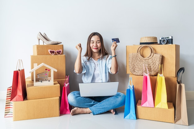 Happy young asian woman with colorful shopping bag, fashion items and stack of cardboard boxes at home
