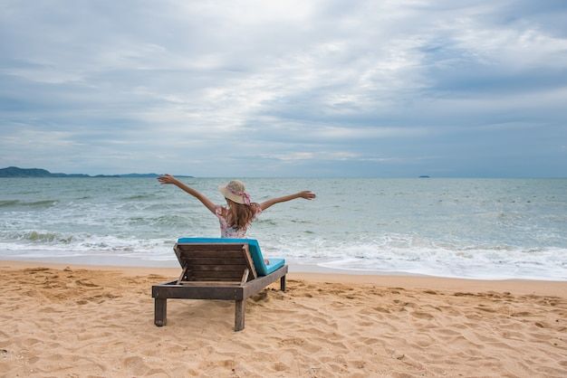 Happy young asian woman with hat relaxing on beach chair and raised hands up.
