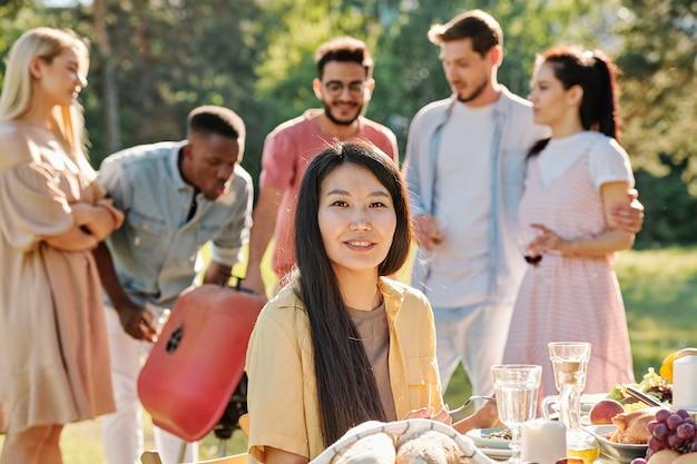 Счастливая молодая азиатская женщина с длинными темными волосами, глядя на вас обслуживаемым столом во время ужина на открытом воздухе