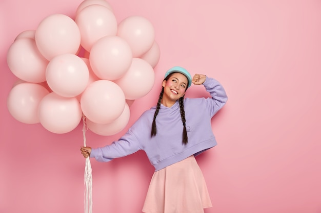 Happy young asian woman with two pigtails, dreams about awesome holiday, carries bunch of air balloons, imagines lovely moment of celebration, isolated on pink wall