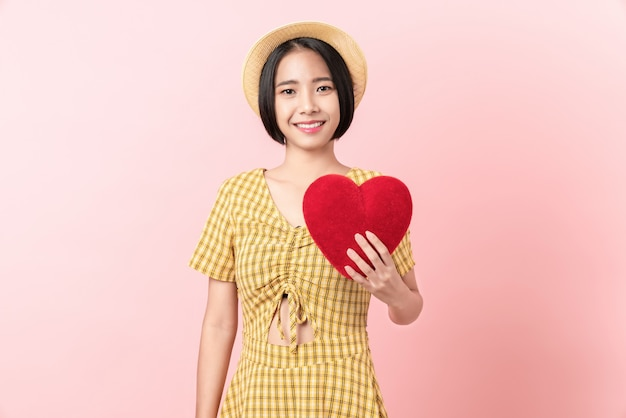Happy young asian woman in a yellow dress holding red hearts and smiling on pink background.