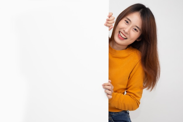 Happy young asian woman in yellow shirt standing behind blank white billboard