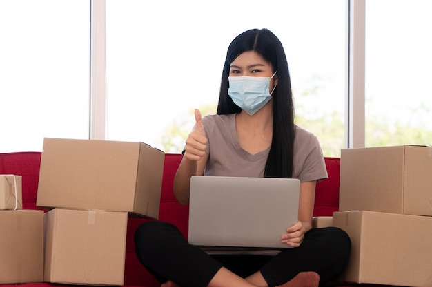 마스크에 행복한 젊은 아시아 여성 기업가는 사업 성공으로 기쁨을 위해 엄지 손가락을 표시합니다.