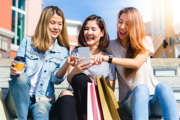Happy young asian women group city lifestyle playing and chatting each other