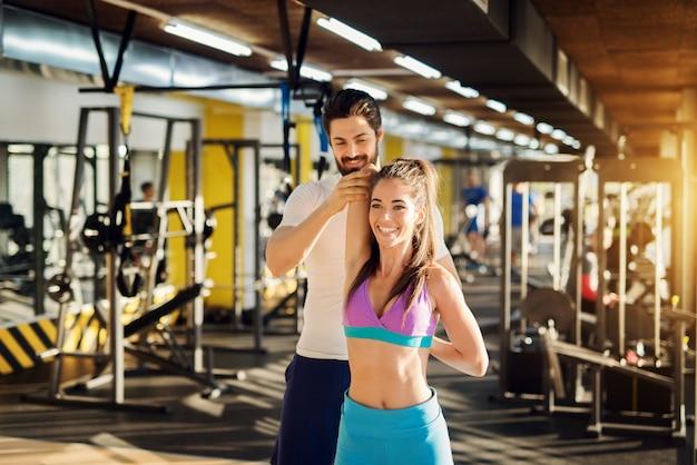 Счастливая молодая спортивная девушка делает растяжку рук, в то время как довольный привлекательный тренер помогает ей в современном тренажерном зале.