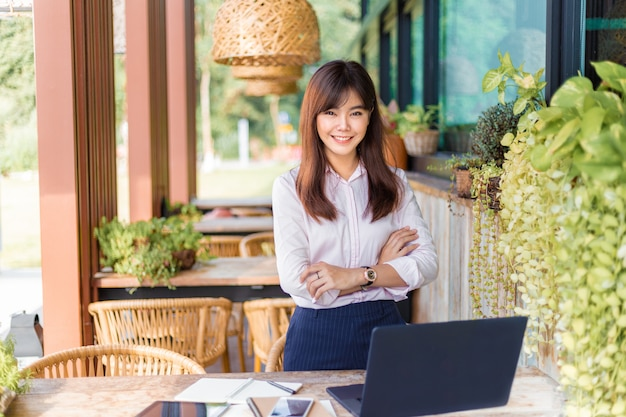 Happy young attractive asian business woman smiling at camera, standing at outdoor patio of her office, happy modern lifestyle