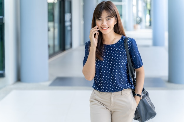 Happy young attractive asian business woman smiling at camera and talking on her cell phone while walking along the hallway of her office building